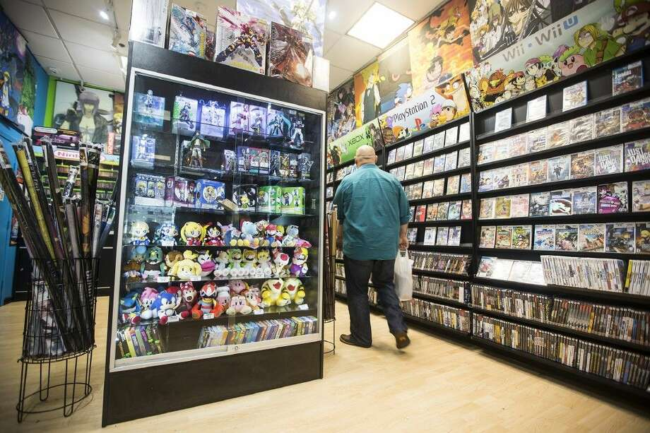 A shopper browses through the collection of classic and modern video games at 3D Games on July 16, 2015, in Deerbrook Mall. Photo: ANDREW BUCKLEY