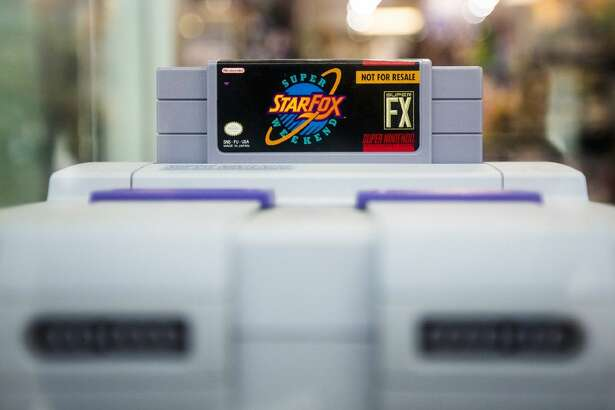 A Star Fox: Super Weekend cartridge, valued at 800, is displayed with a Super Nintendo system in the front window at 3D Games on July 16, 2015, in Deerbrook Mall. It is estimated that only 2000 of the competition cartridges were made and showcases the shop's dedication to classic gaming.
