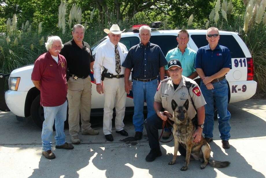 Senna is the new K-9 unit for the Montgomery County Sheriff's Office. Pictured left to right, standing, are Mike Manning, Special Investigations Unit Commander Philip Cash, Montgomery County Sheriff Tommy Gage, Jim Morris, Vernon Miller and Jed Crow. Kneeling are Montgomery County Sheriff's Deputy Tom Thompson and Senna. Photo: Submitted Photo
