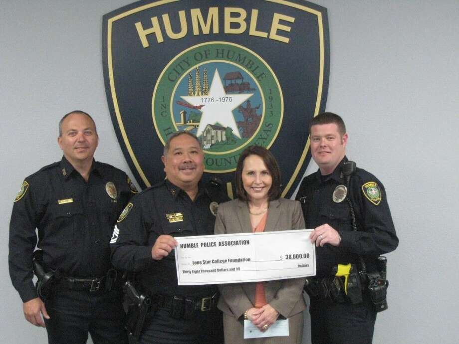 Sergeant Danny Lee, center, along with Humble Police detective Craig Miller, left, and Humble Police officer Jeremy Golden, right, who all serve on the board of the Humble Police association presented a $38,000 check on Monday, March 28 from last year's proceeds to Leah Goss, the Lone Star College Foundation's chief advancement officer.