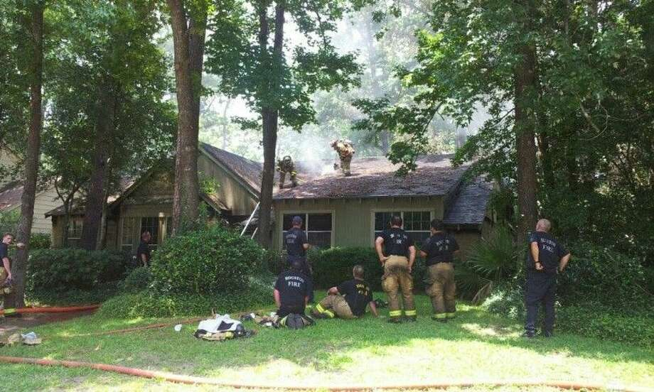Houston Fire Department firefighters works to contain the fire in the 3600 block of Oak Lake Dr. in Kingwood Aug. 15, 2014.