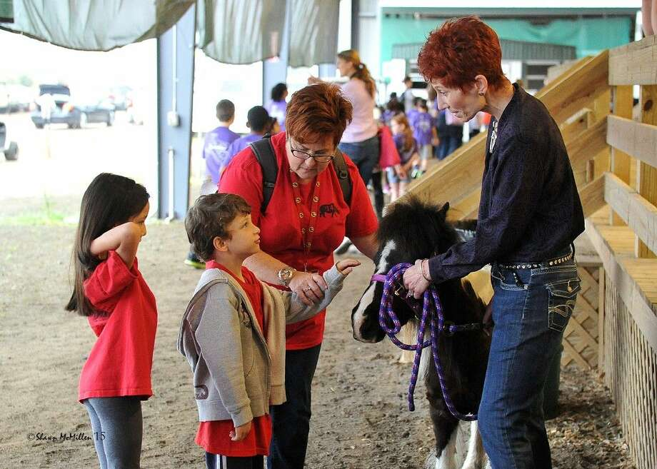 Kay O'Connor (right) watches as students pet one of her therapy ponies at Pin Oak's Education Day at the Great Southwest Equestrian Center March 23.