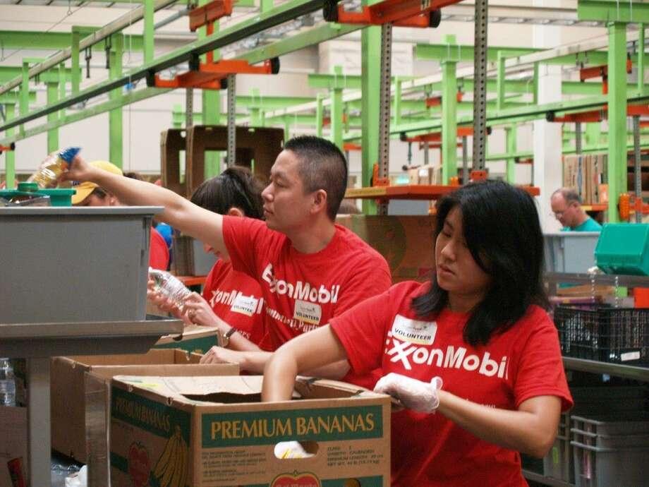 Evaline Tsai (r) and Xiaoying Bao box food at the Houston Food Bank on Friday, July 17.