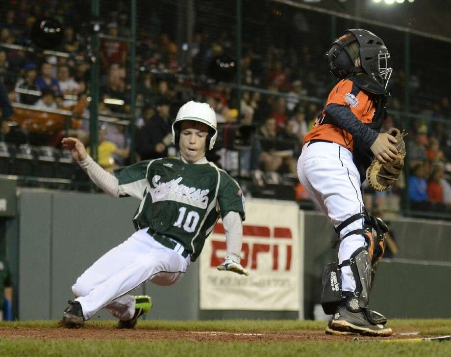 Cole Smajstrla (10) runs behind the catcher to score during Pearland's first game of the 2014 Little League World Series. The team, representing Southwest, beat New England 6-4 (Ralph Wilson)