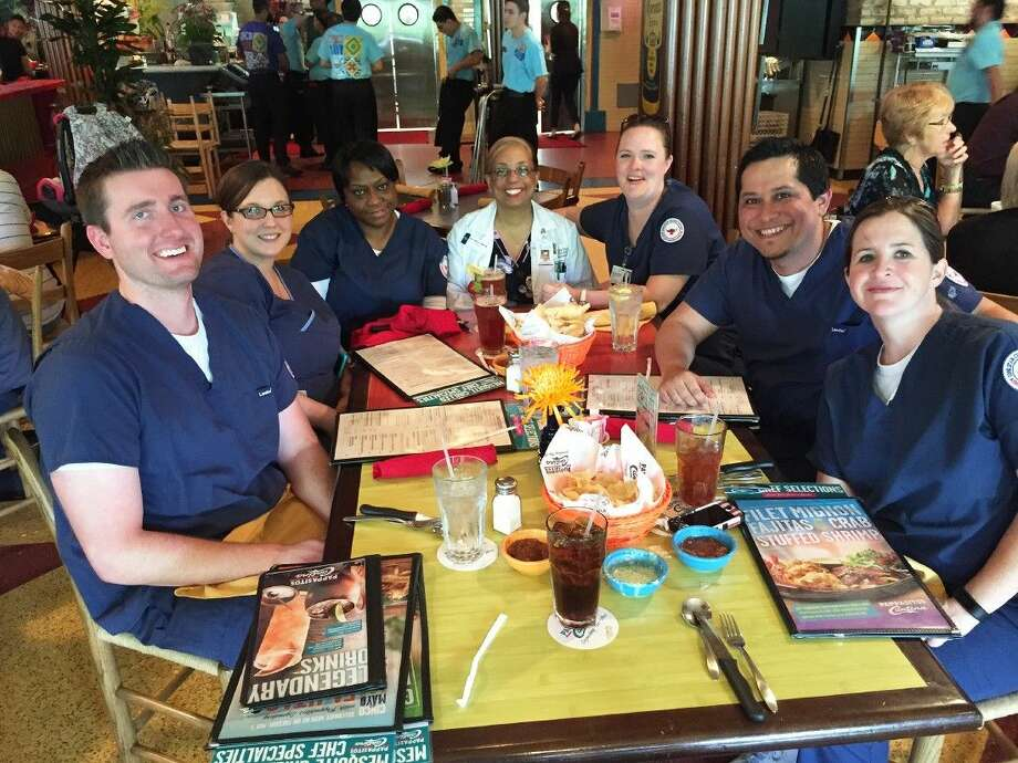 Doris Jackson, center in white jacket, and her students discuss best nurse practices over lunch.