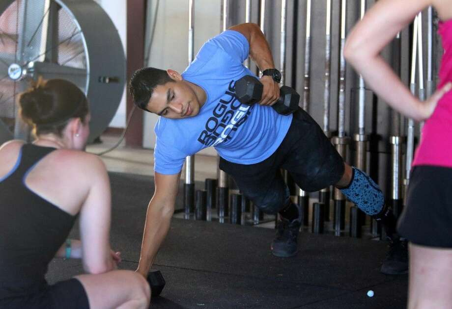 Juan Tello-Salazar demonstrates an exercise at CrossFit GonZstronG in Katy, Texas on Friday, March 27, 2015. Photo: Staff Photo By Alan Warren