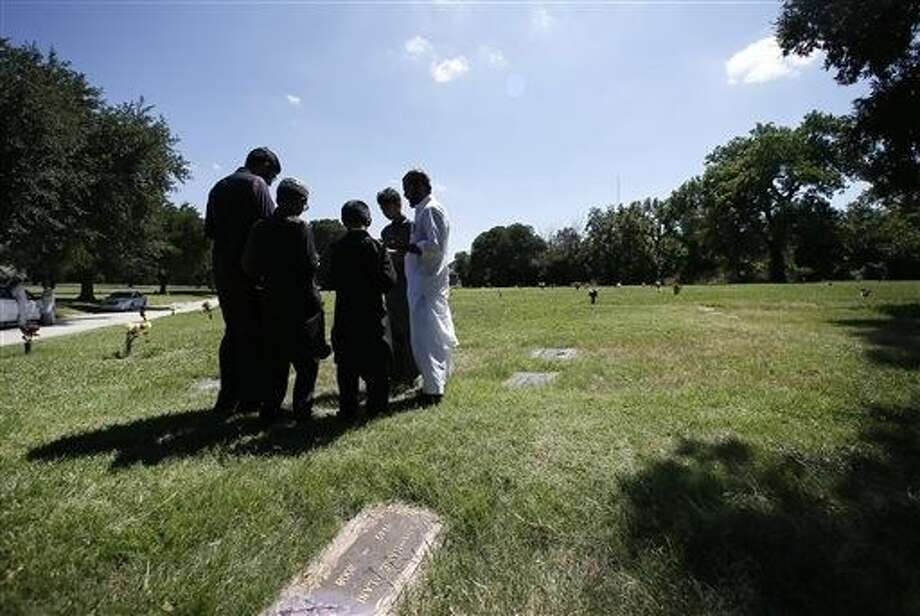 A family gathers in prayer as they visit a family member buried in the Islamic Garden at Restland Cemetery Friday in Dallas. A proposal to bring a Muslim cemetery to Farmersville has stoked fears among residents who are vehemently trying to convince community leaders to block the project. Photo: Tony Gutierrez