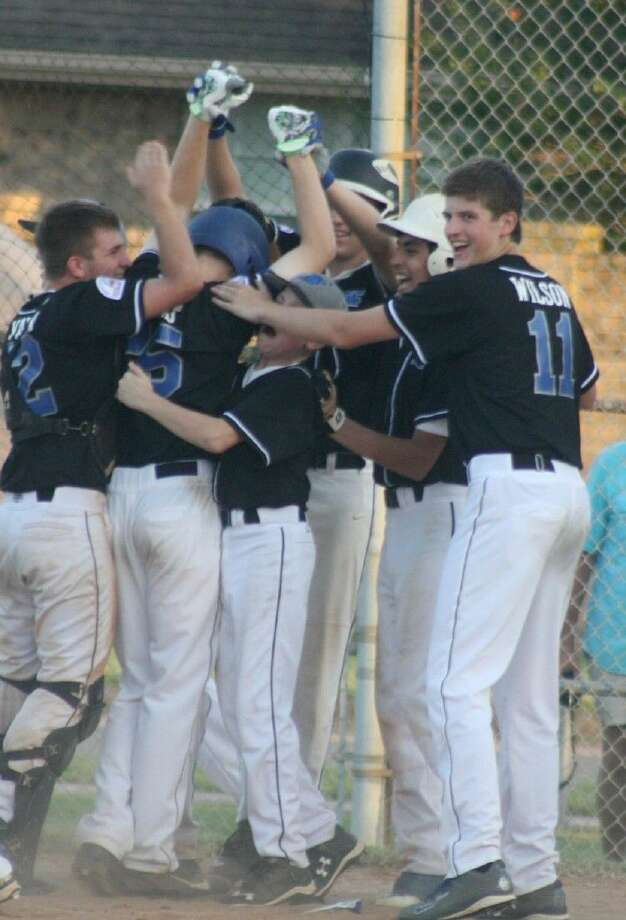 Friendswood players mob Joey Hermes at home plate after he hit a walk-off three-run homer Saturday, giving the team a thrilling 8-5 Pony League win. Photo: Robert Avery