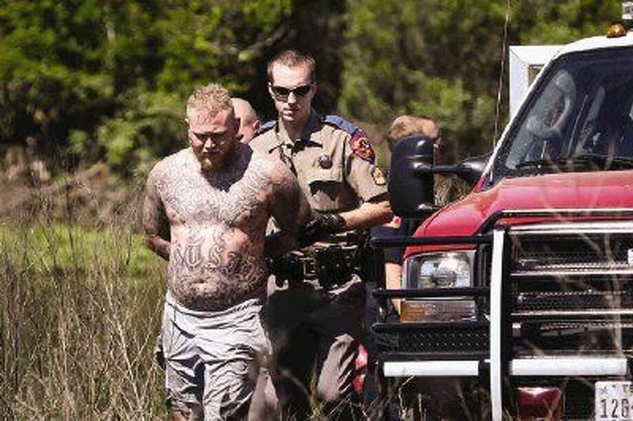 Emergency responders capture a man who allegedly fled from police to an island Monday off of Interstate 45 Southbound between River Plantation Drive and FM 1488. Photo: Michael Minasi