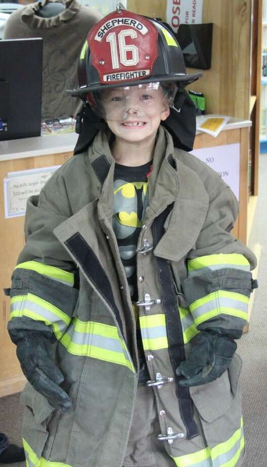 Logan Qualman wears various pieces of firefighting equipment, ranging from the boots to the helmet. Photo: Jacob McAdams
