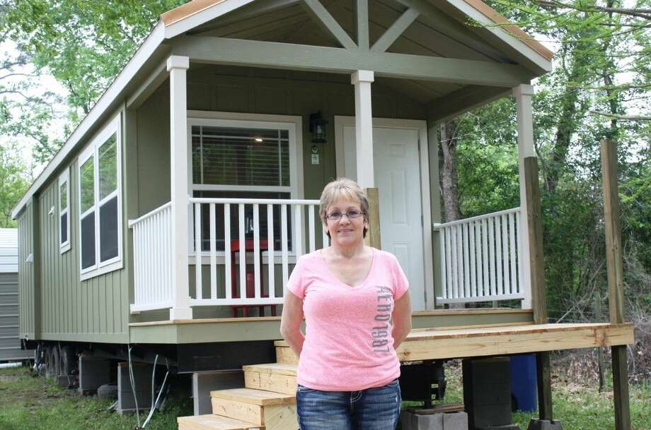Cindy Daniels stands before her 11.5 X 41-foot tiny house on CR 2050 near Hull. Daniels and her husband, Ken, traded their 1,900 square-foot home in Splendora and downsized all of their possessions in order to start anew. Photo: Vanesa Brashier