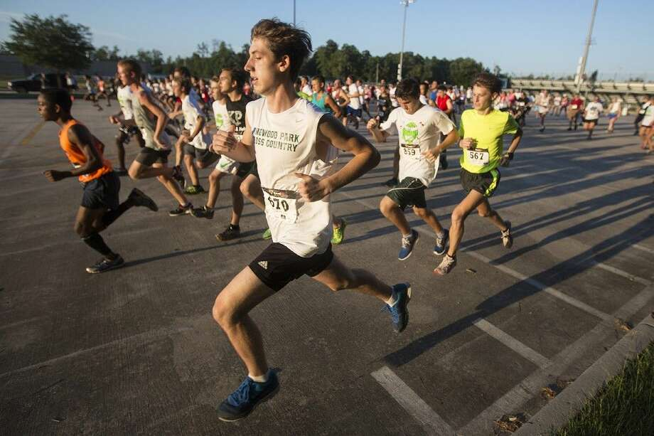 Runners sprint off of the starting line during the Melon Run '14 benefitting the Kingwood Park Cross Country team Aug. 16, 2014, at Kingwood Park High School. Photo: Andrew Buckley