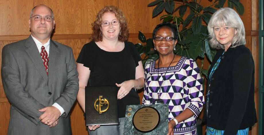 Mike Rodgers, Finance Director for the City of Webster and President of the Government Finance Officers Association of Texas (left) presents the Government Finance Officers Association's Distinguished Budget Presentation Award to City of Friendswood's (from right) Cindy Edge, Director of Administrative Services, Katina Hampton, Deputy Director of Administrative Services - Fiscal Operations, and Jennifer Walker, Budget Manager.