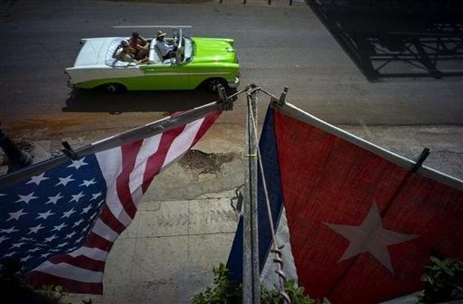 A U.S., and a Cuban national flag, hang from a balcony to mark the restored full diplomatic relations between Cuba and the Unites States, in Old Havana, Monday. The new era began with little fanfare when an agreement between the two nations to resume normal ties on July 20 came into force just after midnight Sunday and the diplomatic missions of each country were upgraded from interests sections to embassies. Photo: Ramon Espinosa