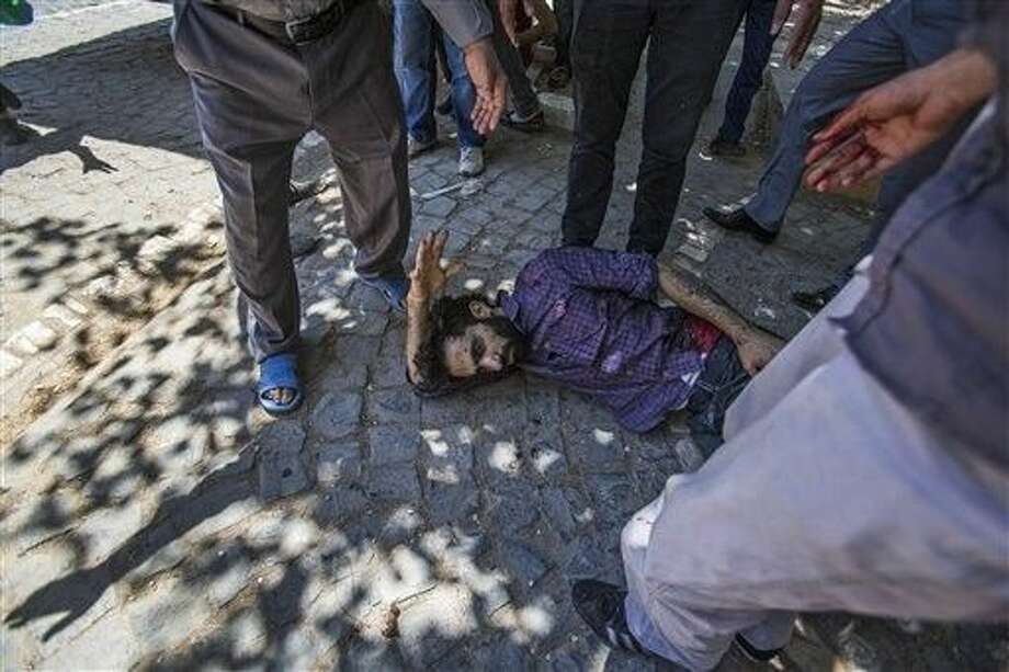 People gather around a man wounded in an explosion that killed dozens of people and injured scores of others, in the Turkish town of Suruc near the Syrian border, Monday. Photo: Zeki Yavuzak
