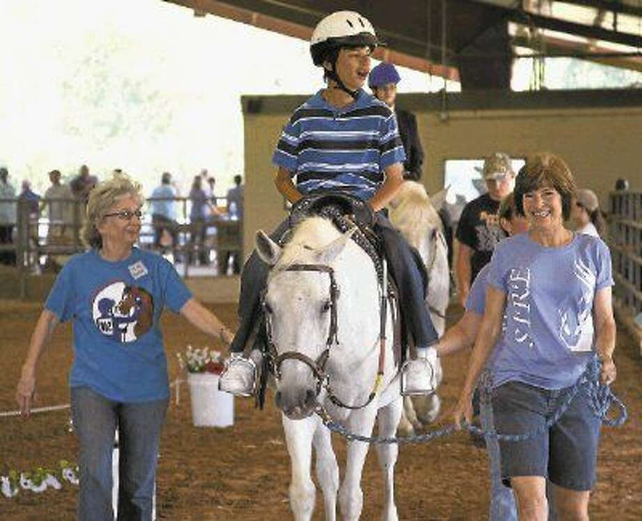 Tyler Overholt is guided on one of SIRE Therapeutic Horsemanship's 34 therapy horses. SIRE's mission is to enrich the lives of individuals with special needs through horsemanship activities, therapy and educational outreach.