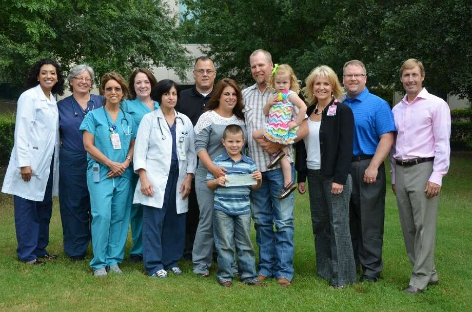 Pictured outside the NICU are (L to R): Pediatric Hospitalist Adriane Garcia, MD; Neonatal Nurse Practitioner Cathy Moody, NNP; NICU nurse Linda Adams, RN; Neonatal Nurse Practitioner M'Ral Lejsek, NNP; Neonatologist Tabasam Roohey, MD; Outpatient Imaging Director Robert Oliver; John and Paige Wolf holding their children Max and Remi; Director of Children's Services Elizabeth Kutchback, RN, BSN; plus Memorial Hermann The Woodlands CFO Randy Reid and CEO Josh Urban. Photo: Submitted Photo