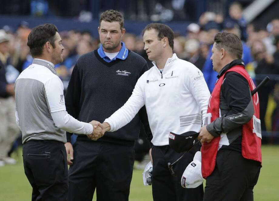 British Open champion Zach Johnson, right, accepts the congratulations of South Africa's Louis Oosthuizen after winning a three-man playoff. Looking on is Australia's Marc Leishman.