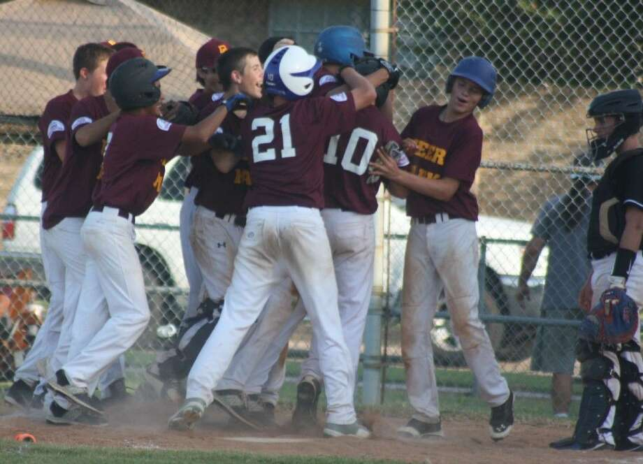 Deer Park players mob Bryce Mead (10) at home plate after he belted a dramatic game-tying two-run homer in the fifth inning against Friendswood Saturday night. Mead's shot traveled an estimated 330 feet to straightaway center field, coming to a stop when it hit a flag pole. Deer Park Pony officials said it was one of the longest home runs ever hit at Varnell Field. Watching the celebration is Friendswood catcher J. P. Yawn. Photo: Robert Avery
