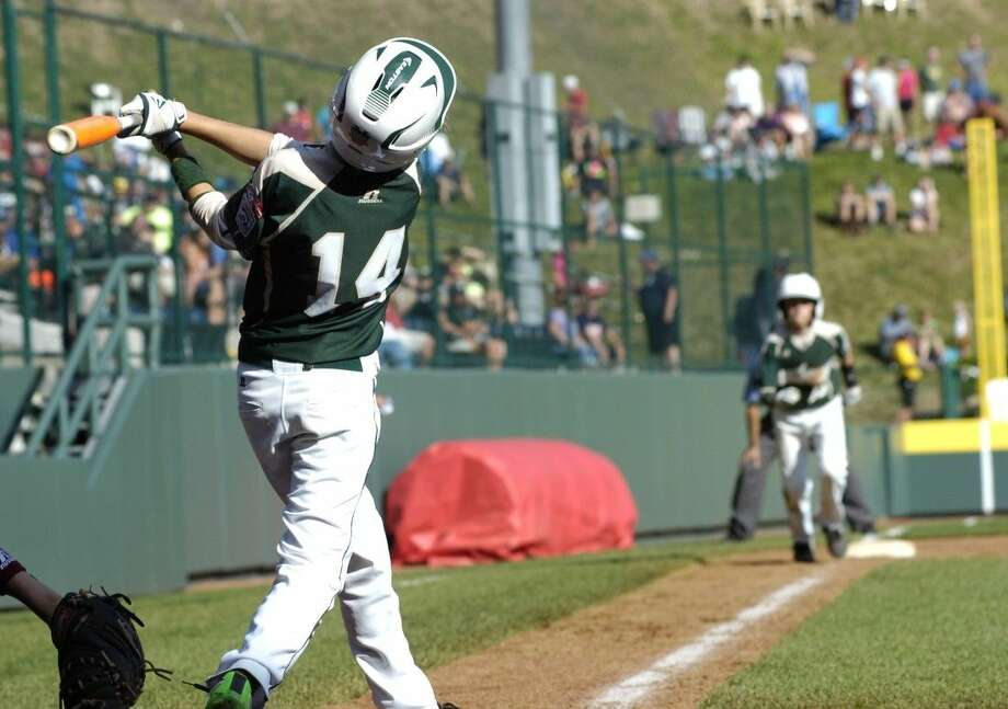 Hunter Dopslauf of Texas swings for the hill as Matthew Adams waits on third ready to head for home during Texas 11-4 win over Washington in the Little League World Series in South Williamsport, PA on Aug. 18, 2014. Photo: MARK NANCE