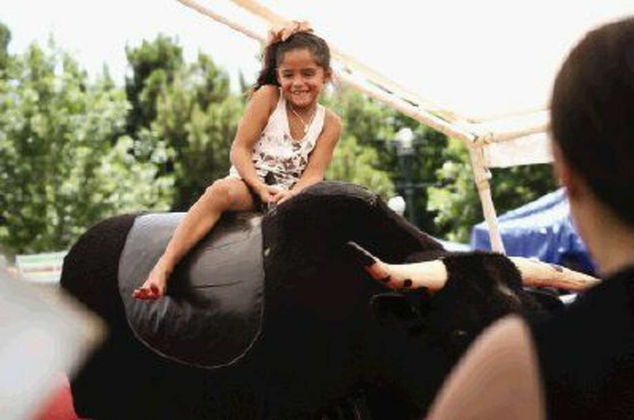 Cassandra Trevino, of The Woodlands, rides a mechanical bull during the Woodlands Family Fun Fest on Saturday at Town Green Park. Photo: Michael Minasi