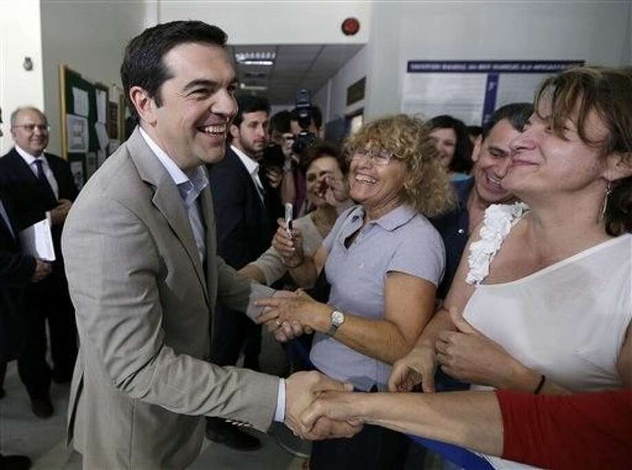 FILE - In this Tuesday, June 2, 2015 file photo, Greece's Prime Minister Alexis Tsipras, left, shakes hands with employees during his visit at the Education Ministry in Athens. Under Alexis Tsipras, Greece slid back into recession, sank deeper into debt and saw unemployment spike. Then after rejecting one painful bailout deal, the radical left leader agreed to a new one with arguably equally harsh terms. It wouldn't be surprising to find Greeks calling for his head by now. But the telegenic prime minister is more popular than ever _ testament to how his defiance of Europe has struck a chord with a nation fed up with sacrifices imposed from outside. Photo: Thanassis Stavrakis