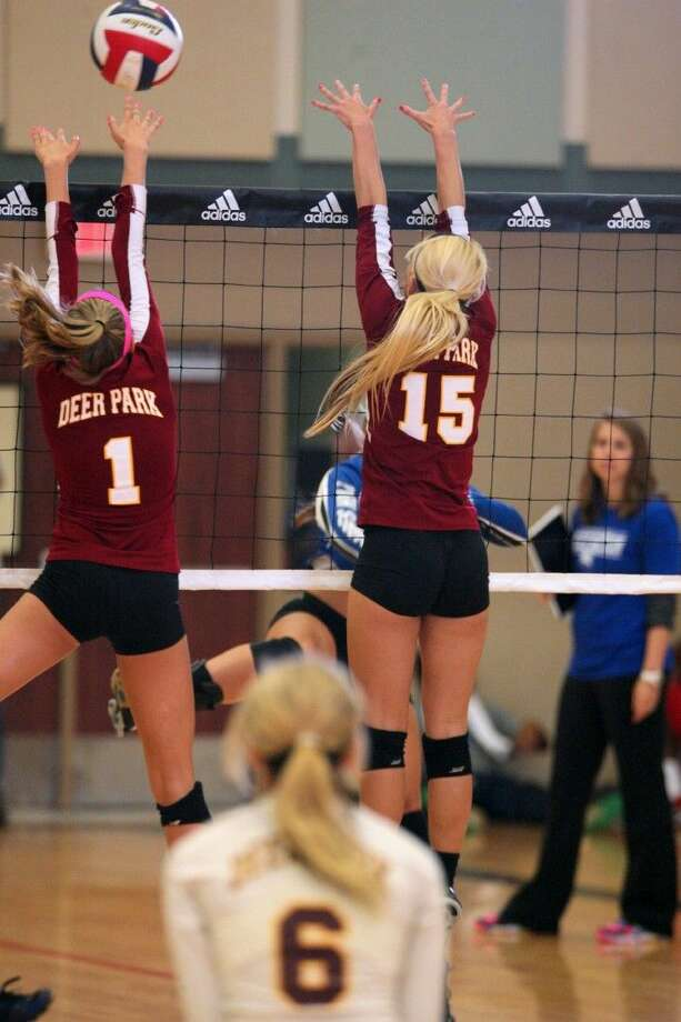 As Darby Shaw looks on, Deer Park's Raegan Hargis (1) and Arika Halling go up for the block attempt during their match with Barbers Hill during Day 2 action at the Adidas Texas Volleyball Invitational. Photo: Kar Hlava