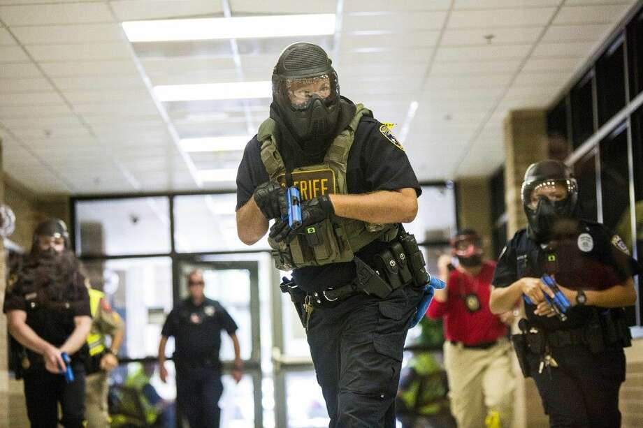 Liberty County sheriff's deputies clear a hallway during an active shooter drill on Aug. 19, 2014, at Cleveland High School. Photo: ANDREW BUCKLEY