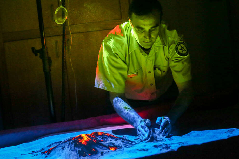 Geospatial Analyst Javier Vara Sanz, with the Texas Forest Service, pushes together mounds of powdered walnut shells to represent varying elevations in a 3D wildfire simulation map on Friday at Lone Star College-Montgomery.