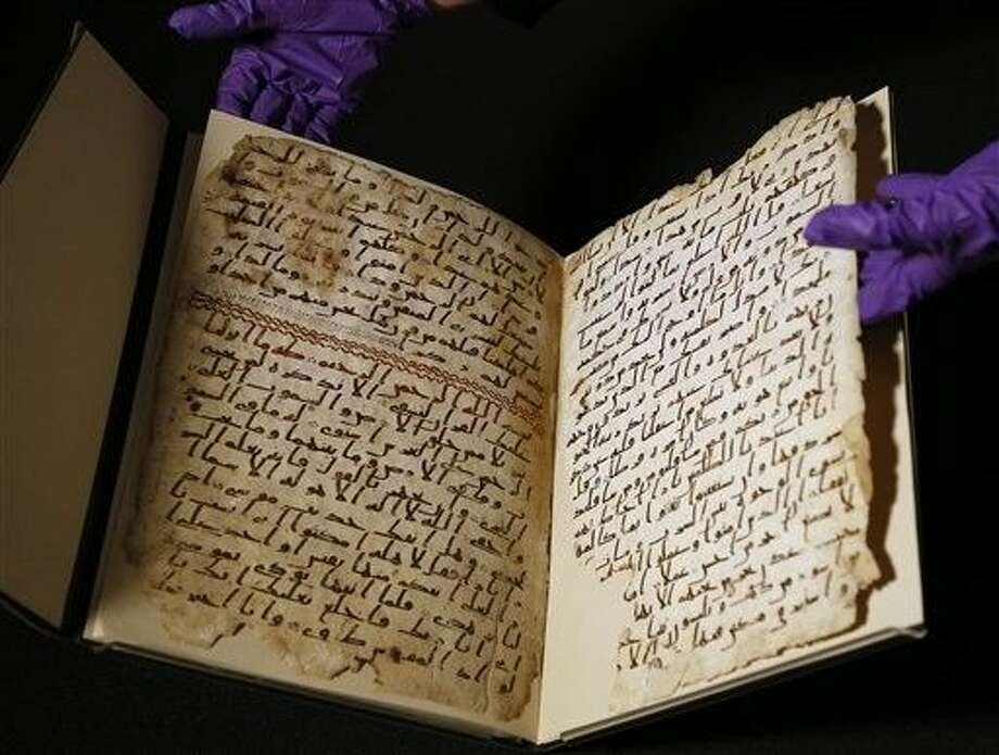 A university assistant shows fragments of an old Quran at the University in Birmingham, in Birmingham central England Wednesday. The University of Birmingham said Wednesday that scientific tests prove a Quran manuscript in its collection is one of the oldest known and may have been written close to the time of the Prophet Muhammad. Radiocarbon testing at Oxford University dated the parchment to the time of the prophet, who is generally believed to have lived between 570 and 632.