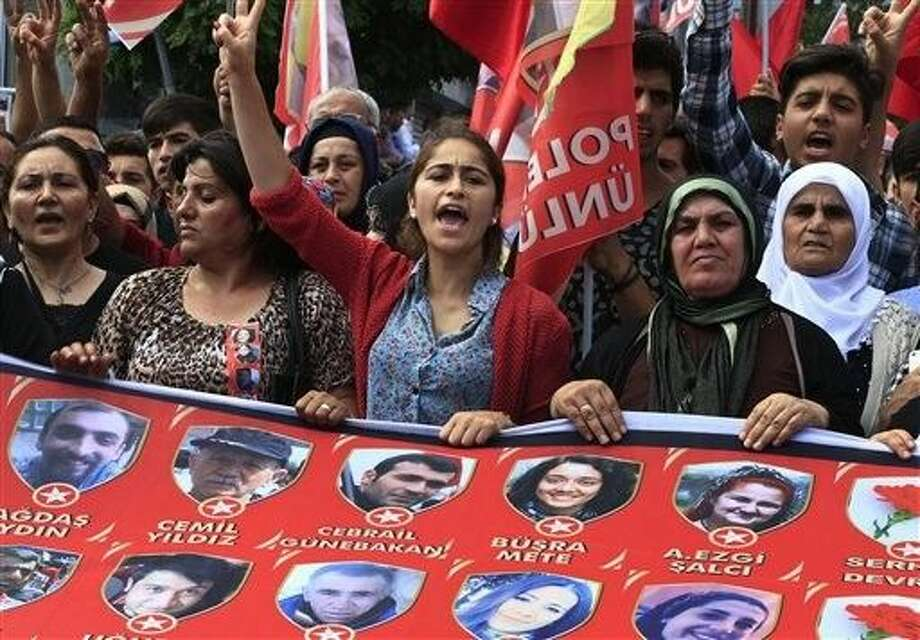 Mourners chant slogans as they carry a banner with pictures of victims of an explosion Monday in Suruc, southeastern Turkey, during a protest in Istanbul, Wednesday. Photo: Lefteris Pitarakis