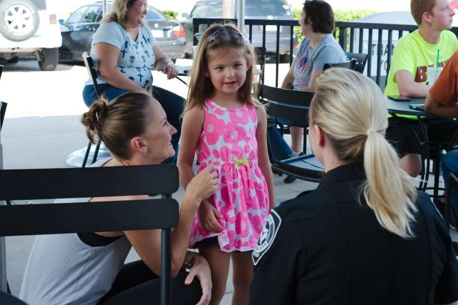 """League City Police Department Officer Reagan Pena introduces herself to Zophia Hedin as mom, Lotus Hedin, sits nearby during the department's """"Coffee with a Cop"""" program Monday, July 20."""