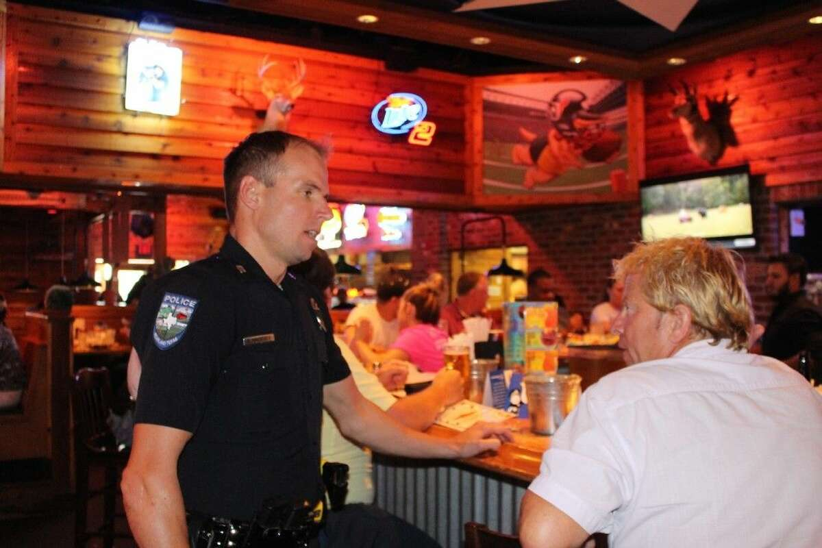 Officer Daniel Hamminga chats with a community member at the bar.