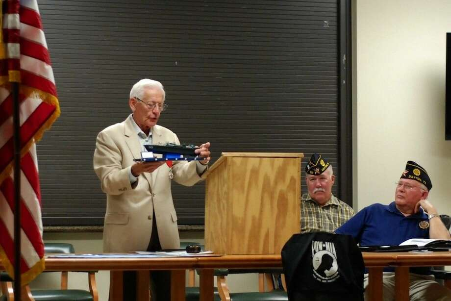 D-Day veteran Clyde Combs holds a model of a PT boat like the one on which he served as a U.S. Navy Petty Officer. Combs spoke Tuesday, Aug. 19, at the American Legion Post 512 in Dayton. Photo: CASEY STINNETT