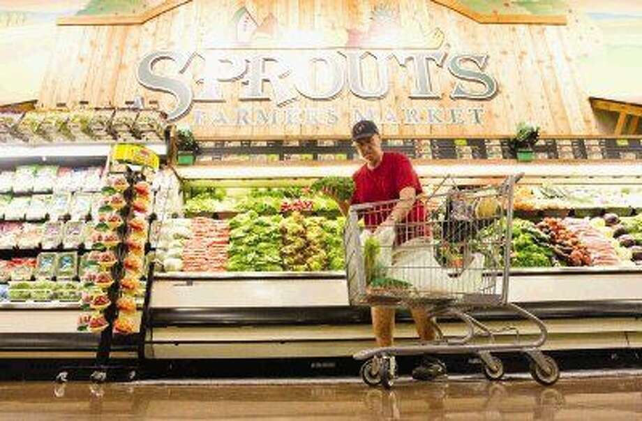 A shopper gathers produces during the opening of Sprouts Farmers Market in Spring Wednesday. Photo: Jason Fochtman