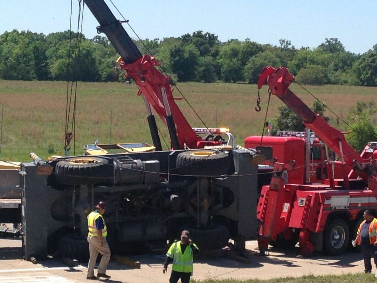 Officials survey the damaged crane and the 18-wheeler that was hit by the crane's arm. Wreckers lifted the crane slightly to allow the flatbed rig to slide out from underneath the boom of the crane.
