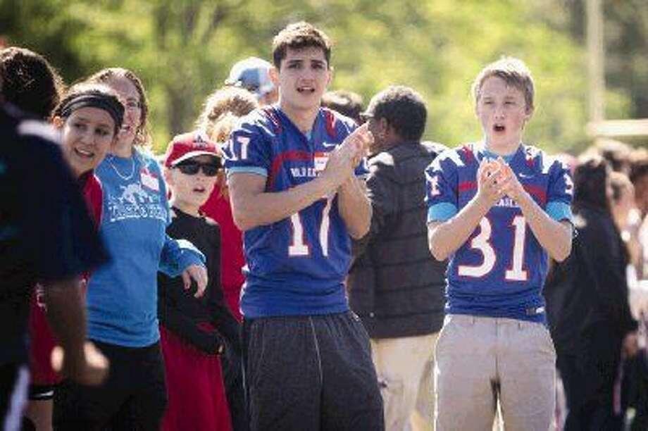 Oak Ridge football players Matt Brown, left, and Cody Stockton, right, cheer on competitors during the annual Kiwanis Invitational Athletics Competition on Saturday, April 2, 2016, at Oak Ridge High School.