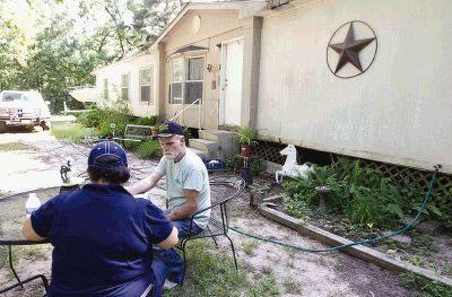 Magnolia resident Bill Englert talks with FEMA Human Service Specialist Nancy Garcia about applying for assistance to repair his property after wind damaged his house during the storms around Memorial Day weekend. Photo: Jason Fochtman