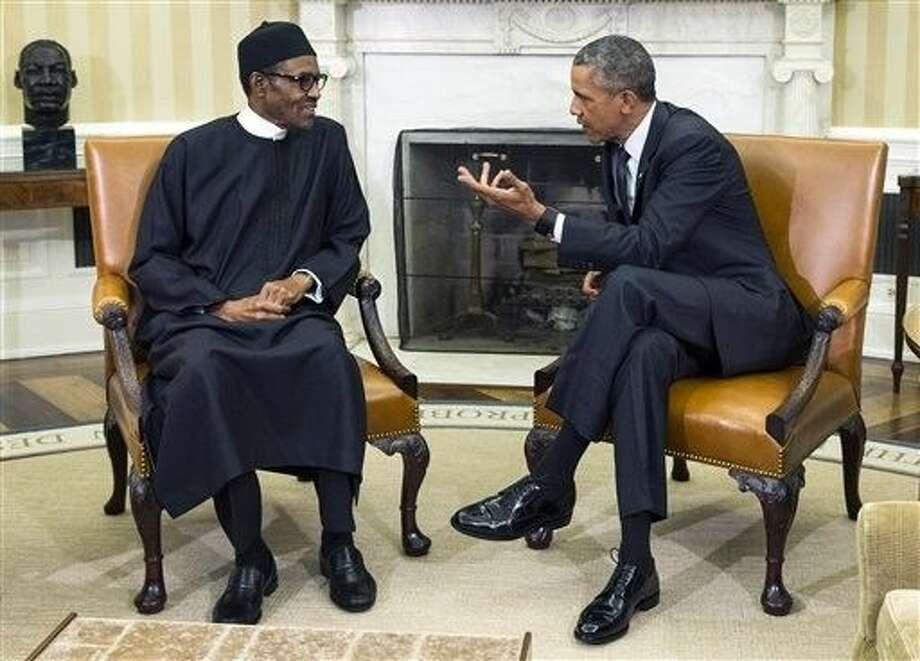 """FILE- In this Monday file photo, President Barack Obama, right, meets with Nigerian President Muhammadu Buhari, in the Oval Office of the White House, in Washington. Bomb blasts at two bustling bus stations killed 29 people and wounded 105, officials said Thursday after Nigeria's new president warned that the U.S. refusal to sell his country strategic weapons is """"aiding and abetting"""" Boko Haram. Photo: Evan Vucci"""