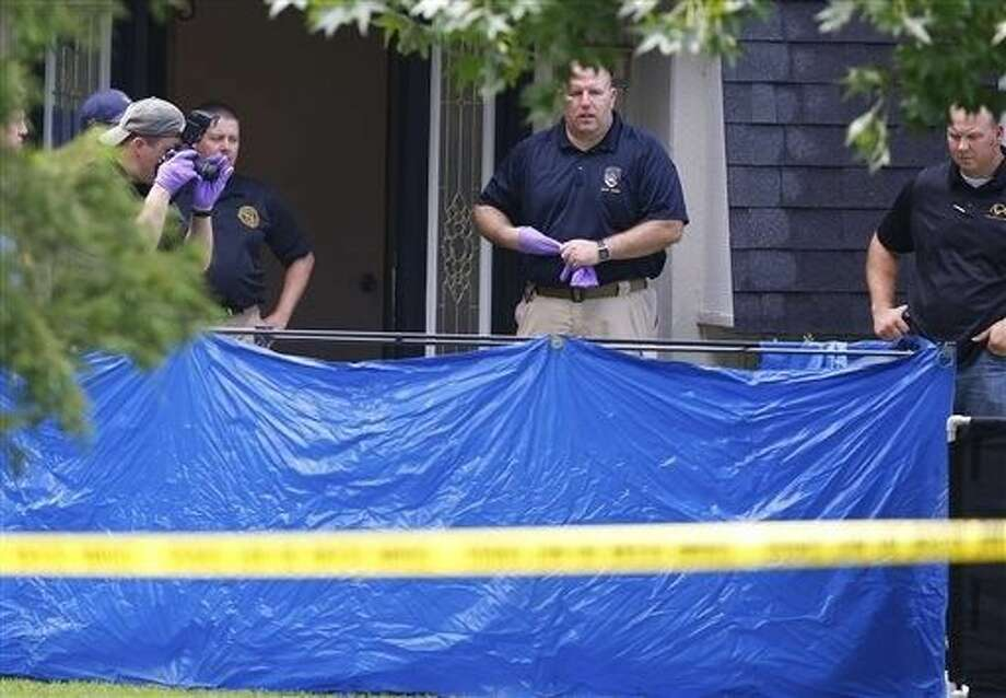 An investigator photographs behind a tarp in the front yard of a home in Broken Arrow, Okla., Thursday where five people were discovered stabbed to death. Two teenagers were taken into custody. Photo: Sue Ogrocki