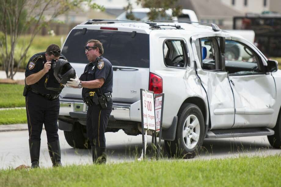 Officers photograph the motocyclist's helmet at the scene of a fatality accident involving a motorcycle and SUV on Aug. 21, 2014, at the intersection of Will Clayton Parkway and Silver Bend Drive. The motorcyclist died at the scene. Photo: Andrew Buckley