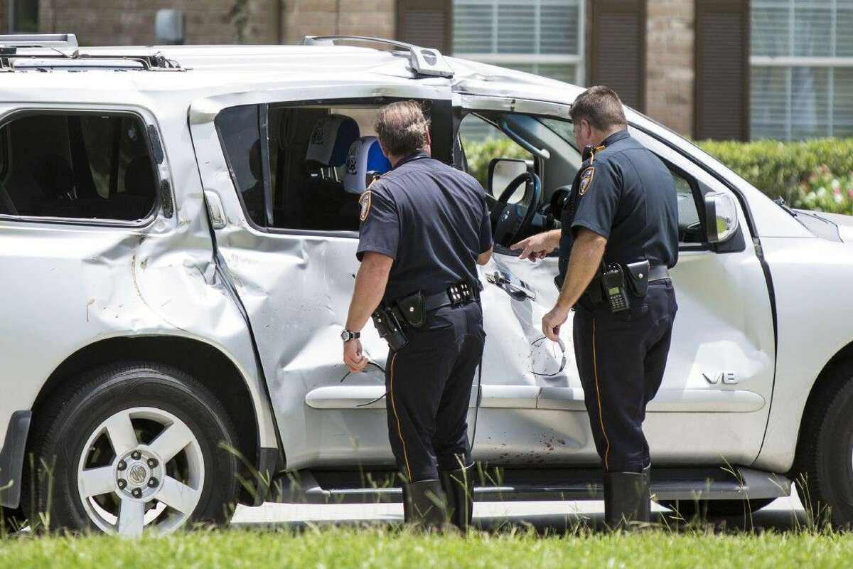 Officers inspect the damage at the scene of a fatality accident involving a motorcycle and SUV on Aug. 21, 2014, at the intersection of Will Clayton Parkway and Silver Bend Drive. The motorcyclist died at the scene.