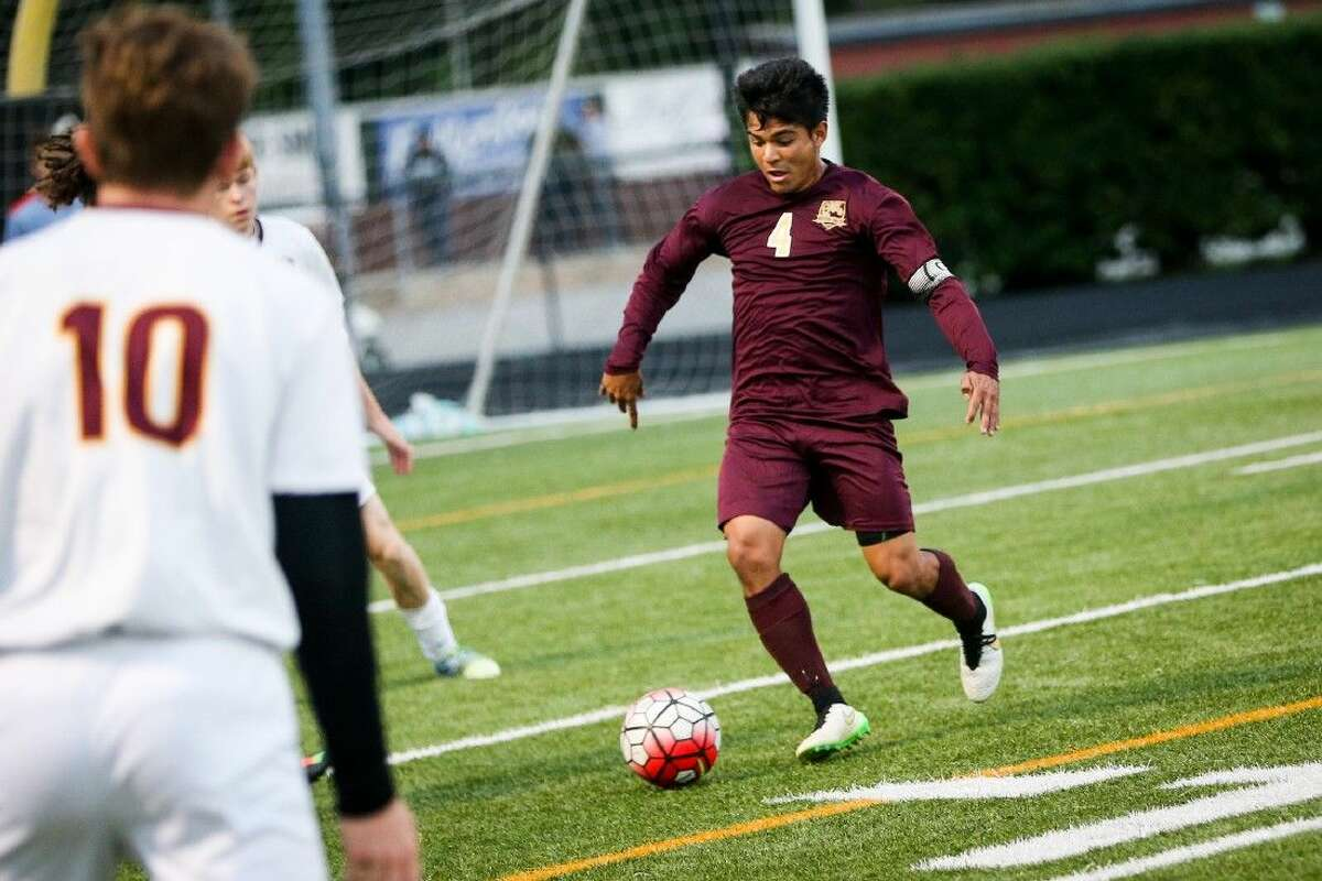 Magnolia West's Bryan Zavala (4) tries to get past A&M Consolidated defenders during a high school boys soccer game on Friday. To view more photos of the game, go to HCNPics.com.