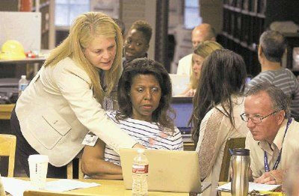 Technology Instructor Susan Haught works with teachers Oberon Coleman and Alan Sweeten during cyber safety training at the High School for Law Enforcement and Criminal Justice on Wednesday, Aug. 13.
