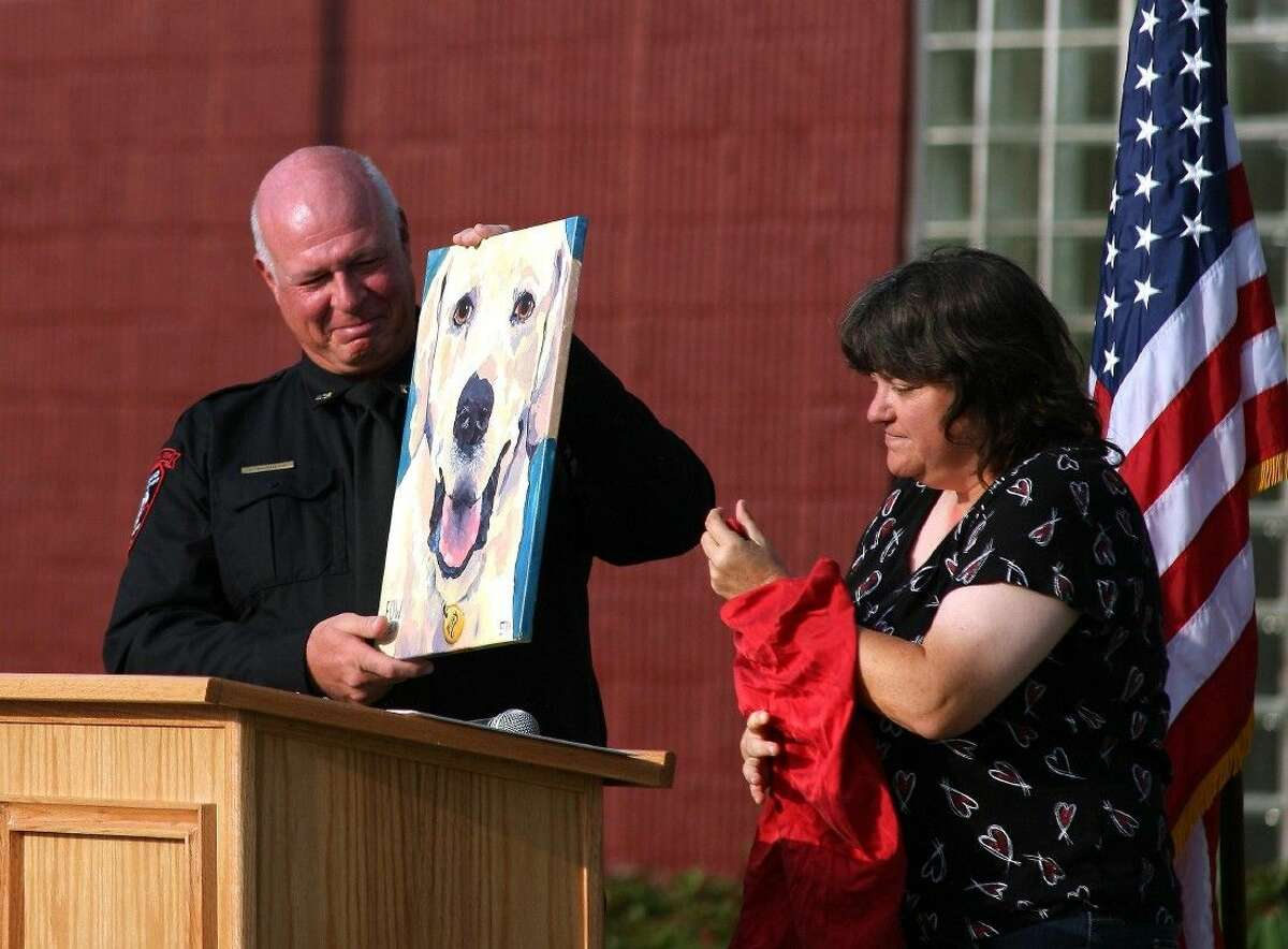 Greg Bozdech tries to hold back his emotions as Lisa Caughlin with Canine Academy Training Center presents Greg with a painting of Buddy.