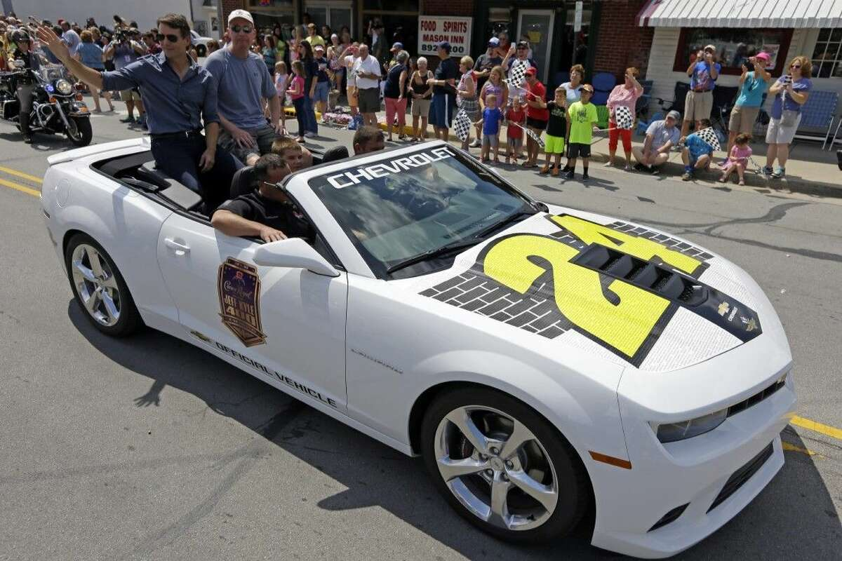 NASCAR driver Jeff Gordon, left, waves to fans along the parade route in Pittsboro, Ind., Thursday.