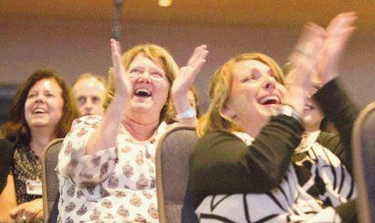 Sheryl Hime, left, and Kim Earthman laugh as they watch a video featuring Conroe ISD Superintendent Dr. Don Stockton during the annual Celebrate Our Schools event at The Woodlands Church Thursday. Go to HCNpic.com to view more photos from the event.