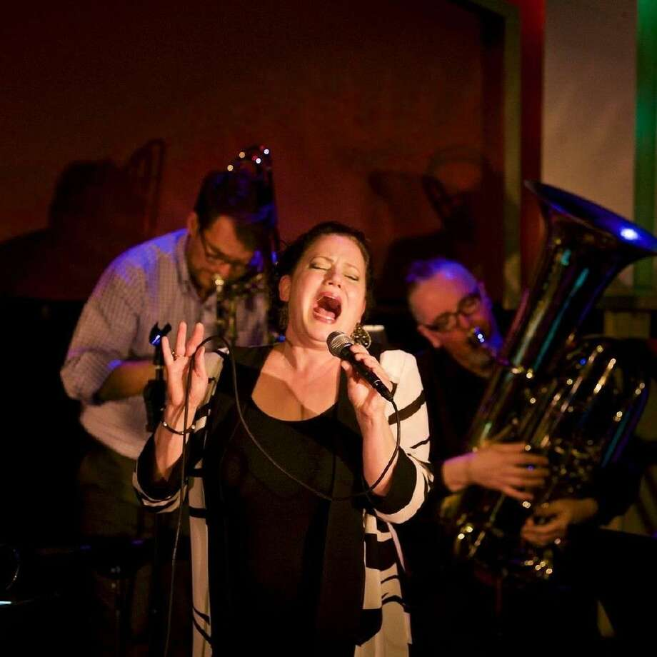 Sheri Lavo performs at the The Larry Slezak Benefit hosted March 20 at Ovations in Rice Village. She is accompanied by Ryan Gabbart on the trombone and Thomas Helton on the tuba, members of the Boomtown Brass Band.