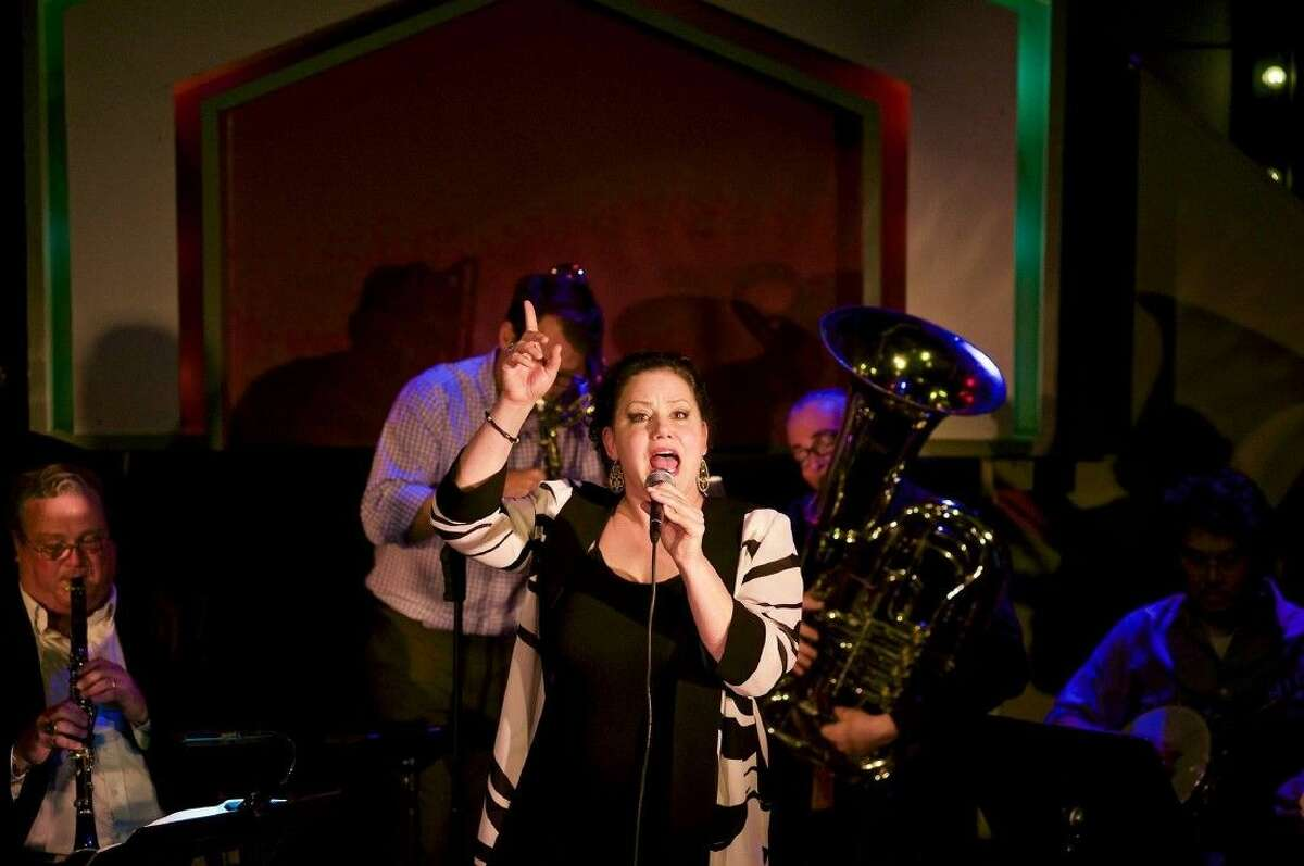 Sheri Lavo sings with the Boomtown Brass Band during the Larry Slezak Benefit hosted March 20 at Ovations in Rice Village. Pictured with Lavo from left are Doug Wright on clarinet, Ryan Gabbart on the trombone, Thomas Helton on the tuba and Mike Viteri on guitar.