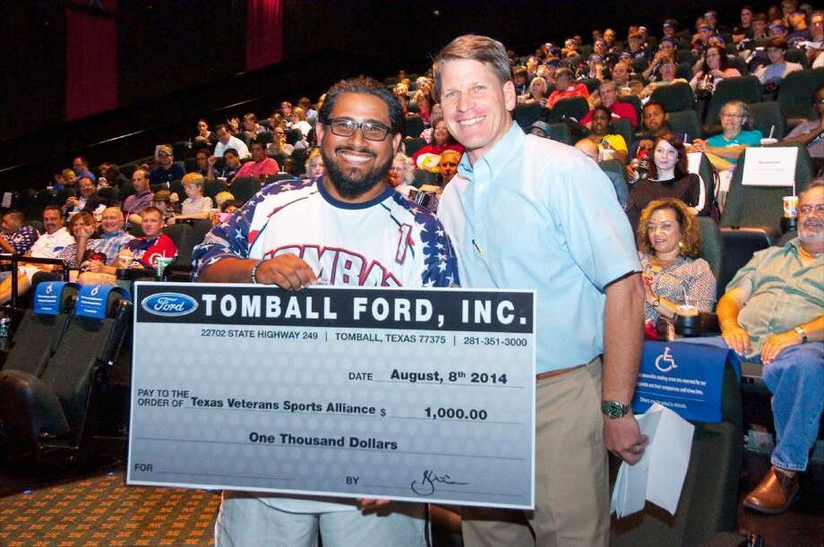 """President of Texas Veterans Sports Alliance, Eddie Vazquez, left, holds up a check for $1,000 from Tomball Ford. Brent Christiansen, right, Tomball Ford's general manager presented the check at an advanced screening of the movie, """"When the Game Stands Tall,"""" on Wednesday, Aug. 20."""